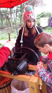 Hannah and Ethan help with the apple press